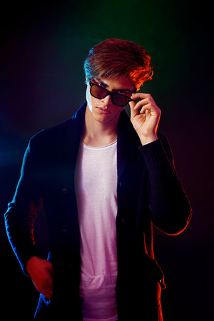 Trendy young man with cool hairstyle wearing black jacket with sunglasses. High Fashion male model in colorful bright neon lights posing on black background. Art design concept Stock Photo