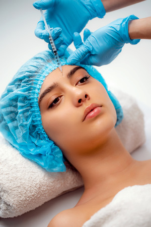 The doctor cosmetologist makes the Rejuvenating facial injections procedure for tightening and smoothing wrinkles on the face skin of a women in a beauty salon. Cosmetology skin care. 版權商用圖片 - 120317512