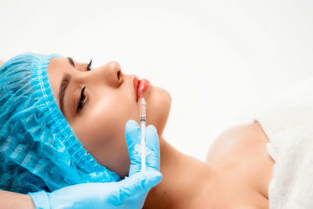 The doctor cosmetologist makes the Rejuvenating facial injections procedure for tightening and smoothing wrinkles on the face skin of a women in a beauty salon. Cosmetology skin care.