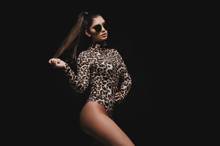 Confident young curvy brunette in sunglasses and leopard bodysuit posing on black background
