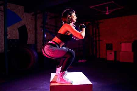 Attractive fit middle age woman doing box jumping at a crossfit style. Female athlete is performing jumps at gym. Stock Photo