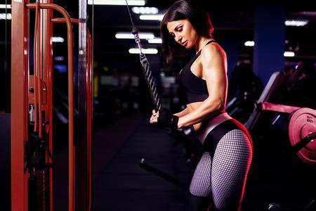 Geeigneter gut ausgebildeter Frauentrainings-Trizeps, der Gewichte in der Turnhalle anhebt Standard-Bild
