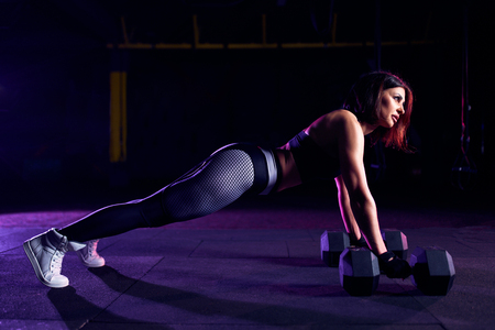Attractive fit middle age woman doing dumbbells plank row exercise lifting dumbbell weights.