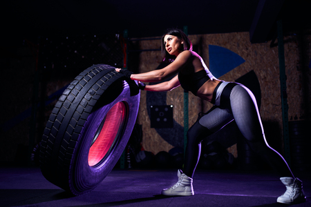 Attractive fit middle age woman athlete working out with a huge tire, turning and flipping in the gym. Crossfit woman exercising with big tire.