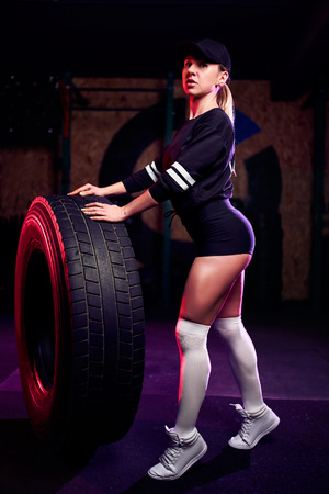 Attractive fit middle age woman athlete posing with a huge tire in the gym. Cross fit woman with big tire.