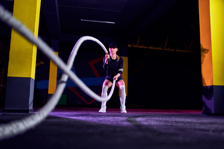 Fitness woman using training ropes for exercise at gym. Athlete working out with battle ropes at cross gym. 写真素材