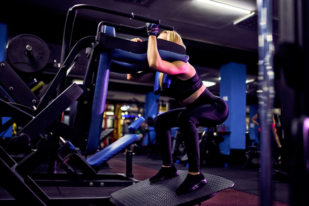 Fitness woman doing lunges exercises for leg muscle workout training in gym.