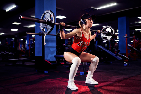 beautiful sporty sexy woman in cap and headphones doing squat workout in gym. 免版税图像