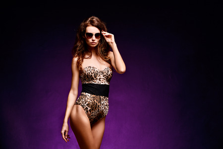 Confident young fit curvy woman in sunglasses and leopard bodysuit posing on studio background. Animal print 版權商用圖片