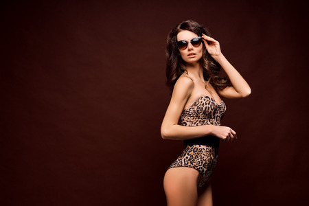 Confident young fit curvy woman in sunglasses and leopard bodysuit posing on studio background. Animal print Banco de Imagens - 121071035