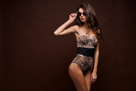 Confident young fit curvy woman in sunglasses and leopard bodysuit posing on studio background. Animal print Banco de Imagens - 121071037