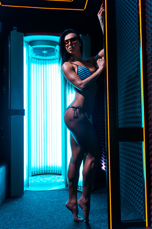 Neon light and girl. Beautiful and athletic woman with healthy body standing in solarium spa salon.