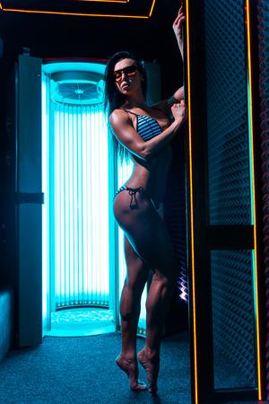 Neonlicht und Mädchen. Schöne und sportliche Frau mit gesundem Körper, die im Solarium-Spa-Salon steht. Standard-Bild