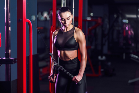 Fit well-trained woman workout triceps lifting weights in gym. Athletic sexy woman doing exercise using machine in gym - side view.