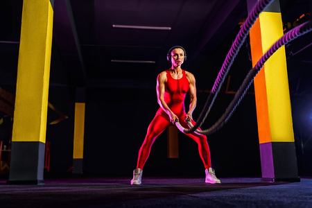 Fitness woman using training ropes for exercise at gym. Athlete working out with battle ropes at gym. 写真素材