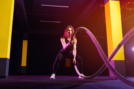 Fitness woman using training ropes for exercise at gym. Athlete working out with battle ropes at cross gym. Imagens
