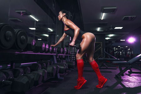 Attractive fit woman in the gym crouches with a barbell. Woman training back. Colored smoke