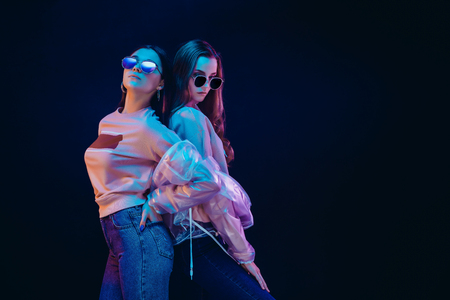 Side view of teen girls in stylish jackets and sunglasses standing on black background in neon illumination