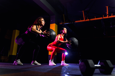 Two Sports women doing squat exercises with fitness ball. Female exercising and stretching with medicine ball at gym.