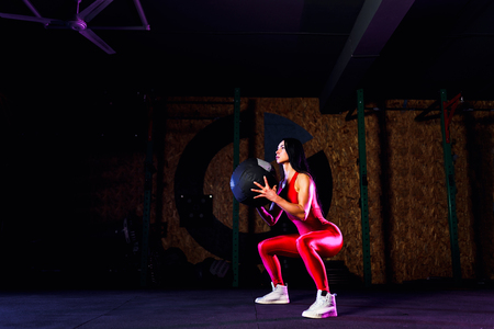 Sportswoman doing squat exercises with fitness ball. Female exercising and stretching with medicine ball at gym.