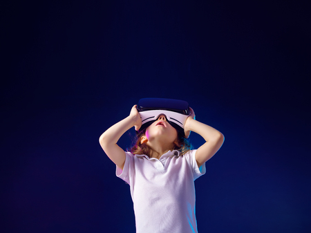 Girl 7 y.o. experiencing VR headset game on colorful background. Child using a gaming gadget for virtual reality. Futuristic goggles at young age. Virtual technology
