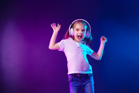 Girl listening to music in headphones on dark colorful background. Cute child enjoying dance music, looking at camera and scream happy while posing on studio background wall. Imagens
