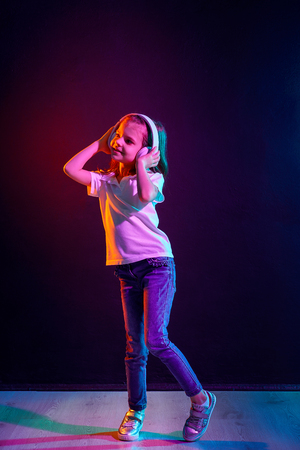 Girl of 7 years old listening to music in headphones and jump on dark colorful background. Neon light. Dancing girl. Happy small girl dancing to music. Cute child enjoying happy dance music. Standard-Bild