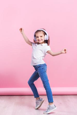 Meisje luisteren naar muziek in koptelefoon een dans. Schattig kind genieten van vrolijke dansmuziek, glimlach, poseren op roze studio achtergrond muur. Stockfoto