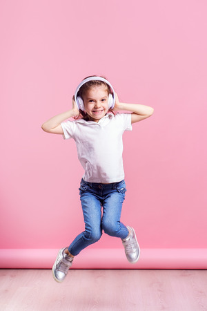 Girl of 7 years old listen to music in wireless headphones and jump on pink background. Dancing girl. Happy small girl dancing to music. Cute child enjoying happy dance music. 写真素材 - 122352868