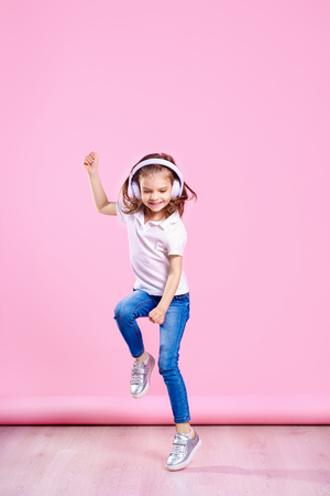Girl of 7 years old listen to music in wireless headphones and jump on pink background. Dancing girl. Happy small girl dancing to music. Cute child enjoying happy dance music. 写真素材 - 122352831