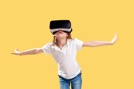 Girl 7 y.o in formal outfit wearing VR glasses putting hands out in excitement isolated on yellow background. Child using a gaming gadget for virtual reality. Virtual technology. Imagens