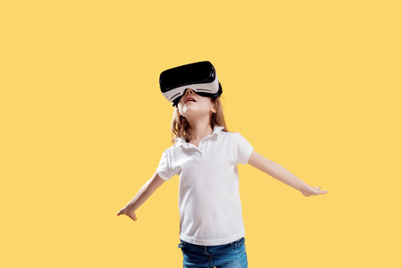 Girl 7 y.o in formal outfit wearing VR glasses putting hands out in excitement isolated on yellow background. Child using a gaming gadget for virtual reality. Virtual technology. Stock Photo - 122352839