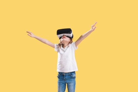 Girl 7 y.o in formal outfit wearing VR glasses putting hands out in excitement isolated on yellow background. Child using a gaming gadget for virtual reality. Virtual technology. 写真素材
