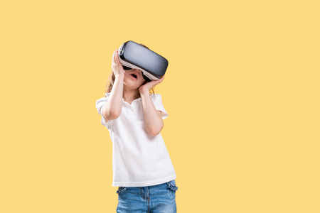 Girl 7 y.o. experiencing VR headset game on yellow background. Surprised emotions on her face.Child using a gaming gadget for virtual reality.Futuristic goggles at young age. Virtual technology Stock Photo