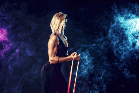 Sexy woman in sportswear using a resistance band in her exercise routine. Young woman performs fitness exercises on black background with smoke. Isolate Stock Photo
