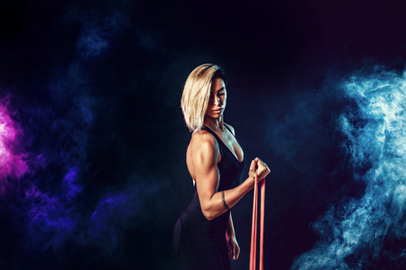 Sexy woman in sportswear using a resistance band in her exercise routine. Young woman performs fitness exercises on black background with smoke. Isolate