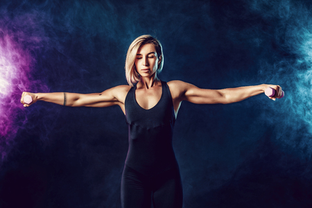 Attractive sporty blonde woman in fashionable sportswear does the exercises with dumbbells. Photo of muscular woman on dark background with smoke. Strength and motivation.