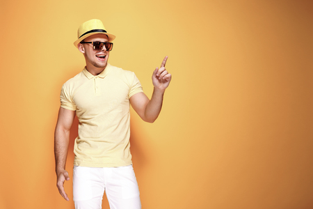 Positive young male in trendy outfit smiling and pointing away while standing against yellow background Stock Photo