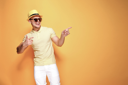 Positive young male in trendy outfit smiling and pointing away while standing against yellow background