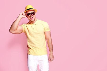 Positive young male in trendy outfit - yellow shirt, sunglasses, white shorts, holding straw hat smiling and looking at camera while standing against pink background