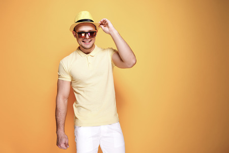 Positive young male in trendy outfit - yellow shirt, sunglasses, white shorts, holding straw hat smiling and looking at camera while standing against yellow background Foto de archivo