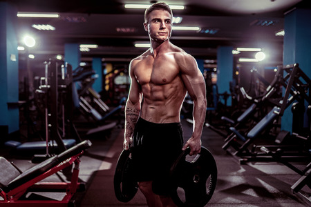 Side view of a caucasian handsome fitness model posing in the gym. Man on diet flexing muscles and six pack abs Stock Photo - 124524531