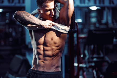 Side view of a caucasian handsome fitness model posing in the gym. Man on diet flexing muscles and six pack abs Stock Photo