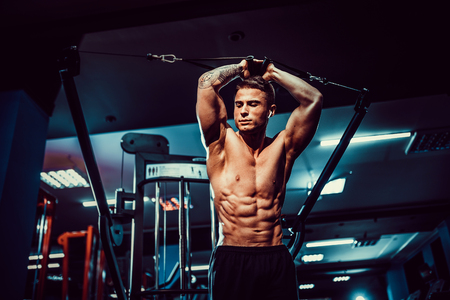 Handsome shirtless fitness model in gym training six pack in crunch machine. close up abs concept. healthcare lifestyle.