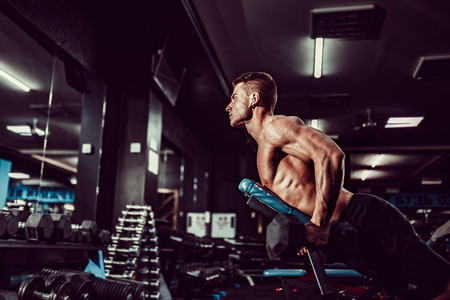 Young muscular man doing hard exercise with dumbbells for rear deltas of shoulders on training bench at the gym.