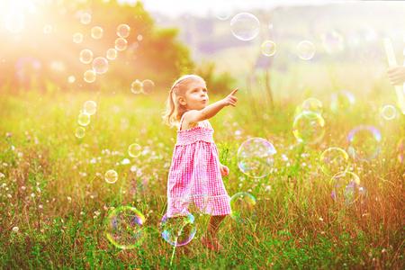 Niña divertida atrapando pompas de jabón en el verano en la naturaleza. Concepto de infancia feliz.
