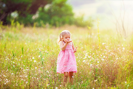 Funny little girl playing in the summer on nature. Happy childhood concept.