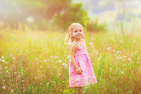 Funny little girl catching soap bubbles in the summer on nature. Happy childhood concept.