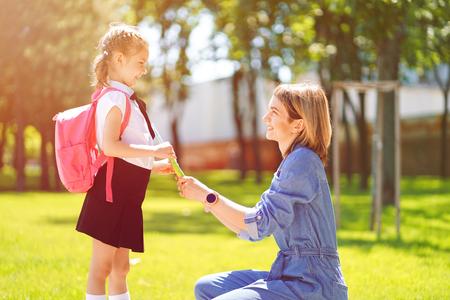 Premier jour à l'école. La mère dirige une petite écolière en première année. Femme et fille avec sac à dos derrière le dos. Début des cours. Premier jour d'automne Banque d'images