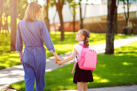 Parent and pupil of primary school go hand in hand. Woman and girl with pink backpack behind the back. Beginning of lessons. First day of fall Foto de archivo